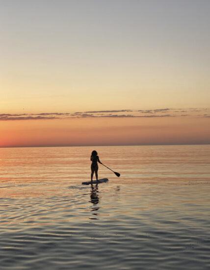 Mujer practicando paddle surf durante el amanecer